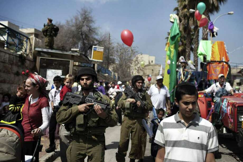 Israeli soldiers guard Jewish settlers celebrating the annual Purim parade on March 8, 2012, in the divided West Bank city of Hebron. Purim commemorates the salvation of the Jews from the ancient Persians as described in the biblical book of Esther. AFP PHOTO/MENAHEM KAHANA Photo: MENAHEM KAHANA, AFP/Getty Images / AFP