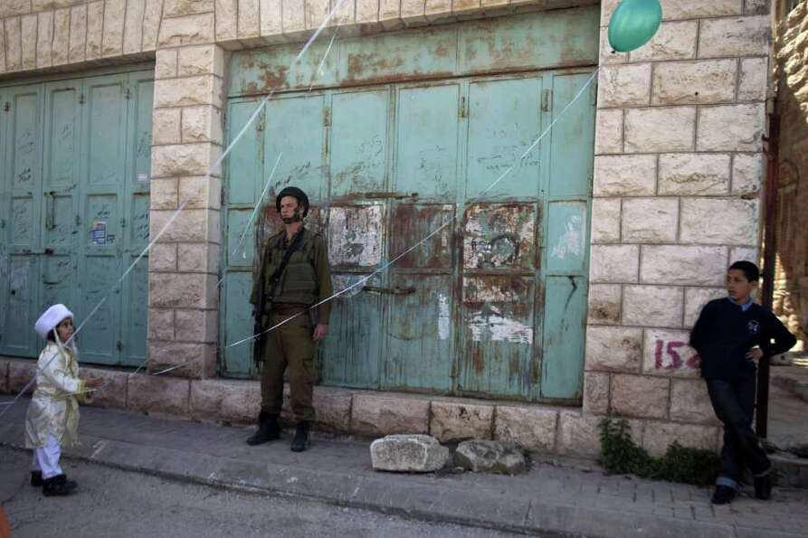 An Israeli soldier stands guard between a Jewish settler's a chid (L) and a Palestinian boy (