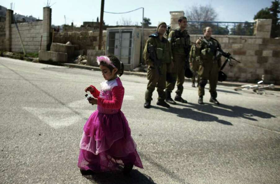 Israeli soldiers keep guard as an Israeli settler's daughter, wearing a costume, celebrates the annu