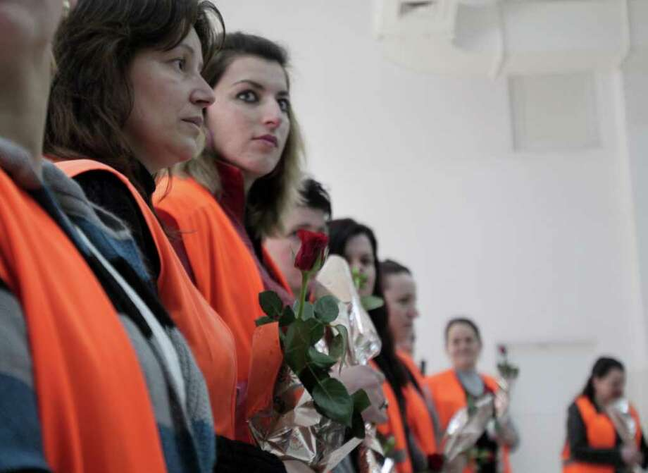 Inmates in the Women's Correctional Facility in Lipjan hold roses received as a symbolic gift from Kosovo Justice Minister  on International Women's Day on Thursday, March  8, 2012. The date is celebrated in Kosovo and Kosovo officials chose to visit the prison to stress the importance of reintegrating the convicts into Kosovo life after they serve their sentences. ( AP Photo) Photo: Associated Press / AP