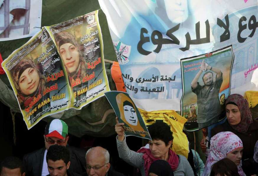 Palestinian women hold posters of Hana Shalabi, a Palestinian prisoner jailed in Israel and who has