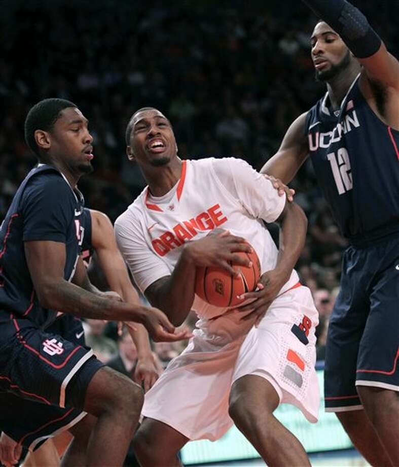 Syracuse's Kris Joseph, center, tries to put up a shot while being defended by Connecticut's Roscoe Smith, left, and Andre Drummond during the quarterfinal round of the Big East NCAA college basketball conference tournament in New York, Thursday, March 8, 2012. (AP Photo/Seth Wenig) / AP2012