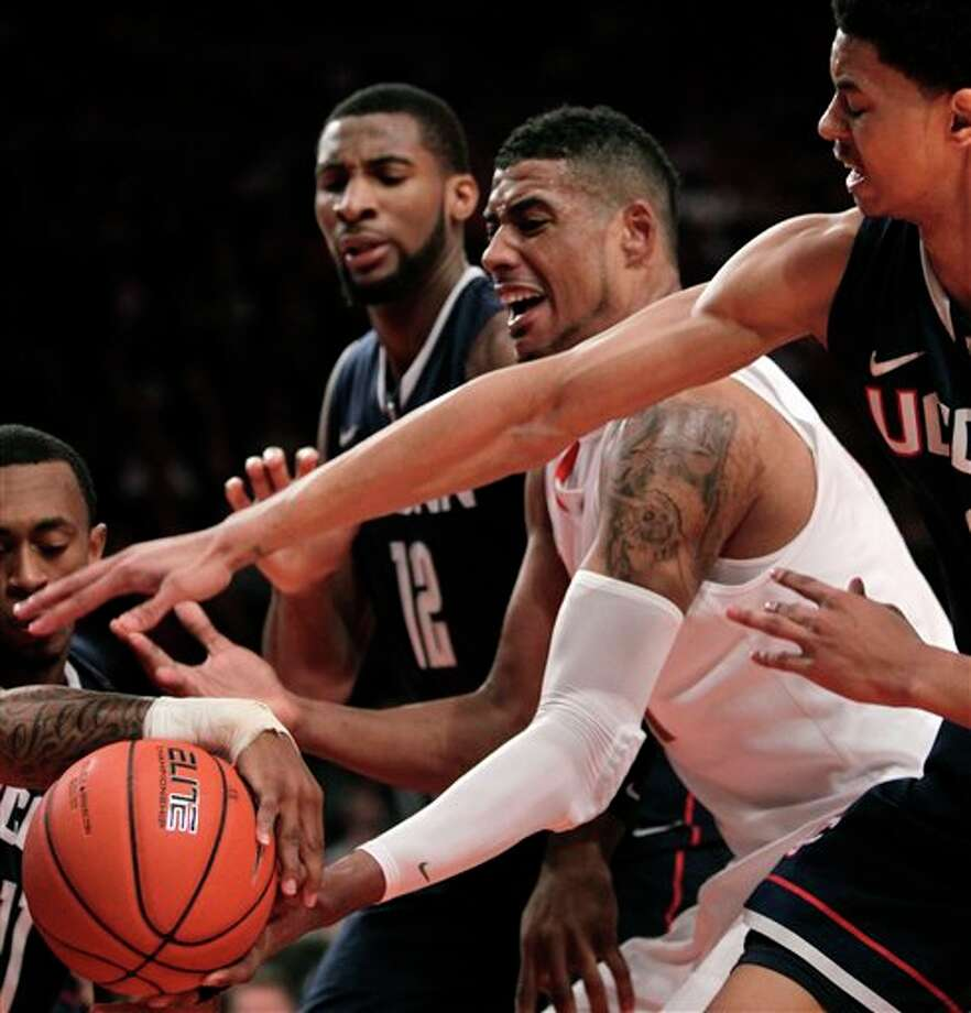 Syracuse's Fab Melo, second from right, battles for a rebound with Connecticut's Jeremy Lamb, right, and Andre Drummond during the quarterfinal round of the Big East NCAA college basketball conference tournament in New York, Thursday, March 8, 2012. (AP Photo/Seth Wenig) / AP2012