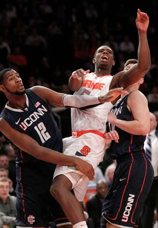 Syracuse's C.J. Fair, center, looks after a shot while being defended by Connecticut's Andre Drummond, left, and Tyler Olander during the quarterfinal round of the Big East NCAA college basketball conference tournament in New York, Thursday, March 8, 2012. (AP Photo/Seth Wenig) / AP2012