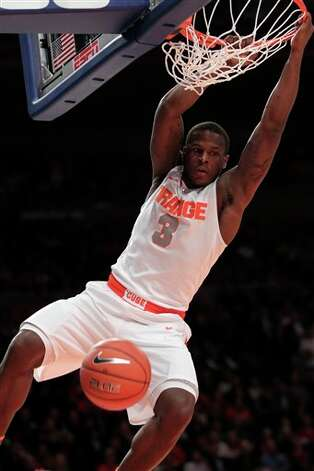 Syracuse's Dion Waiters hangs on the rim after slamming the ball during the  quarterfinal round of the Big East NCAA college basketball conference  tournament against Connecticut in New York, Thursday, March 8, 2012. (AP  Photo/Seth Wenig)