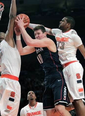 Syracuse's Fab Melo, left, and James Southerland, right, block Connecticut's Tyler Olander during the quarterfinal round of the Big East NCAA college basketball conference tournament in New York, Thursday, March 8, 2012. Syracuse beat Connecticut 58-55. (AP Photo/Seth Wenig)