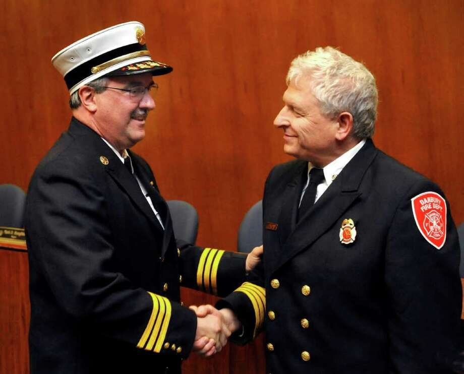 Bernie Meehan is congratulated by Danbury Fire Chief Geoff Herald after taking the oath of office as Danbury's new assistant chief. Photographed at Danbury City Hall Thursday, March 8, 2012. Photo: Michael Duffy