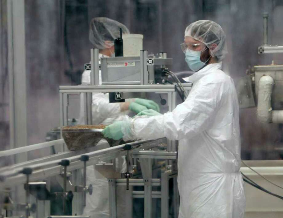 Jake Winiski performs quality control in a cleanroom inspecting a tray of mycelium and other raw materials that will age to become an eco-friendly packaging material at Ecovative Design in Green Island, N.Y., on Thursday, Feb. 9, 2012. Photo: AP