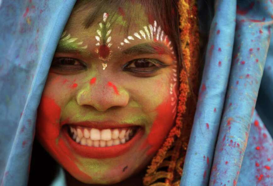 An Indian tribal girl, her face smeared with color and wearing festive finery, participates in a cul