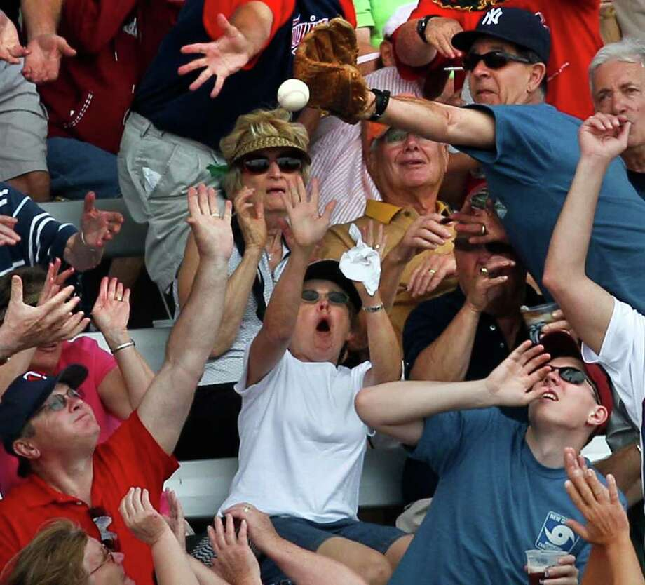 Fans jockey for position for a foul back during a Twins-Rays spring training game in Fort Myers, Fla. Photo: AP