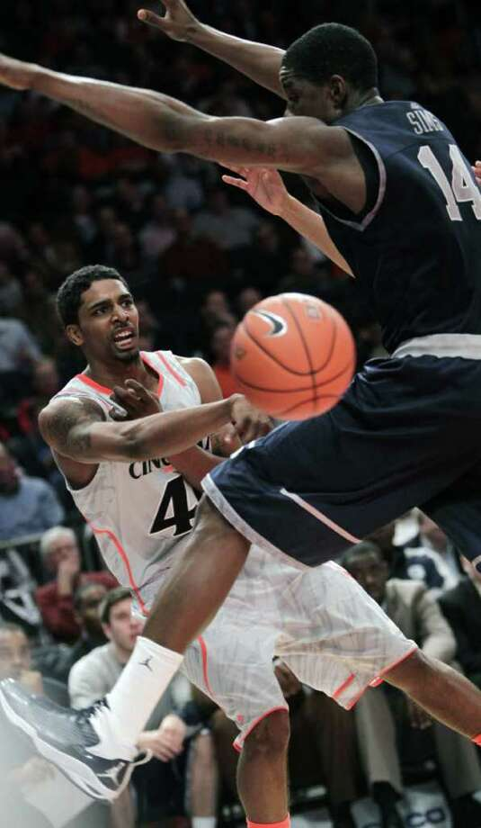 Cincinnati's Jaquon Parker, left, passes around Georgetown's Henry Sims during the quarterfinal round of the Big East NCAA college basketball conference tournament in New York, Thursday, March 8, 2012. Photo: Seth Wenig