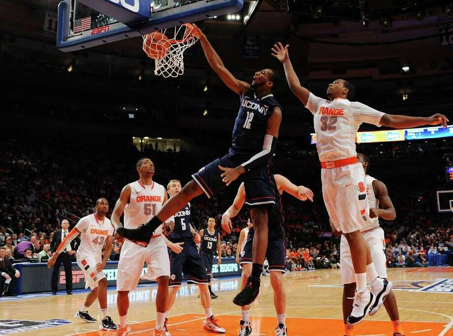 UConn's Andre Drummond dunks over Syracuse's Kris Joseph during Thursday's loss to the top-seeded Orange in the quarterfinals of the Big East Men's tournament at Madison Square Garden. Photo: Michael Heiman/Getty Images / 2012 Getty Images
