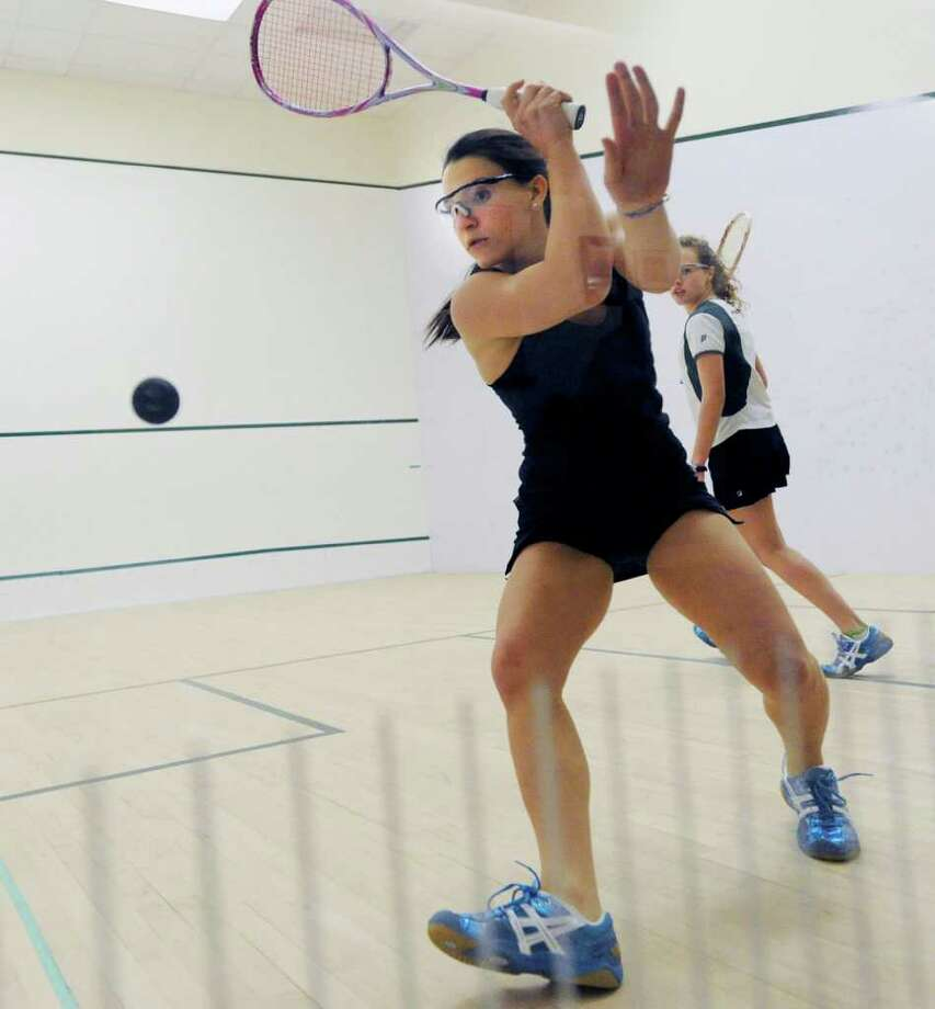 Jocelyn Lehman, left, of Greenwich Academy, hits against Krystina Miles of Convent of the Sacred Heart during squash match between Convent of the Sacred Heart and Greenwich Academy at Greenwich Academy, Thursday night, Dec. 8, 2011. Photo: Bob Luckey / Greenwich Time