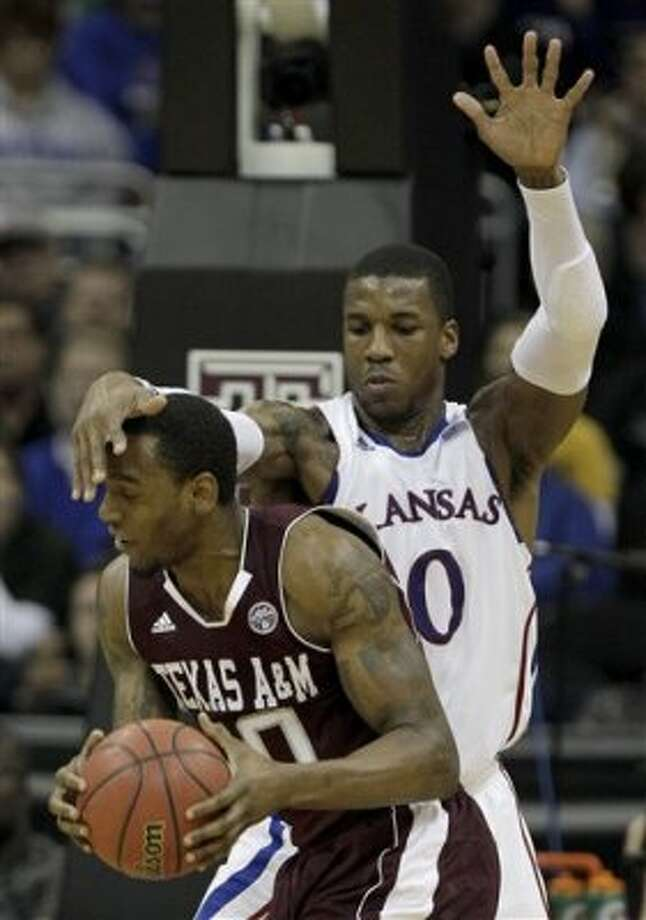 Kansas forward Thomas Robinson, right, pressures Texas A&M forward David Loubeau, left, during the second half of an NCAA college basketball game in the Big 12 Conference tournament on Thursday, March 8, 2012, in Kansas City, Mo. Kansas won the game 83-66. (AP Photo/Charlie Riedel) (AP)