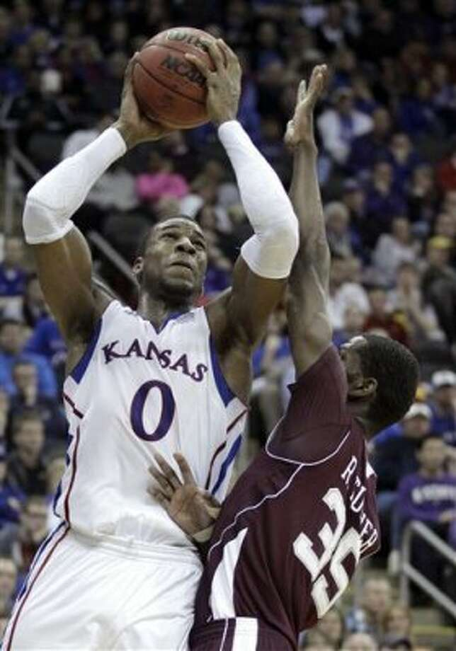 Kansas forward Thomas Robinson (0) puts up a shot under pressure from Texas A&M forward Ray Turner (35) during the second half of an NCAA college basketball game in the Big 12 Conference tournament, Thursday, March 8, 2012, in Kansas City, Mo. (AP Photo/Charlie Riedel) (AP)