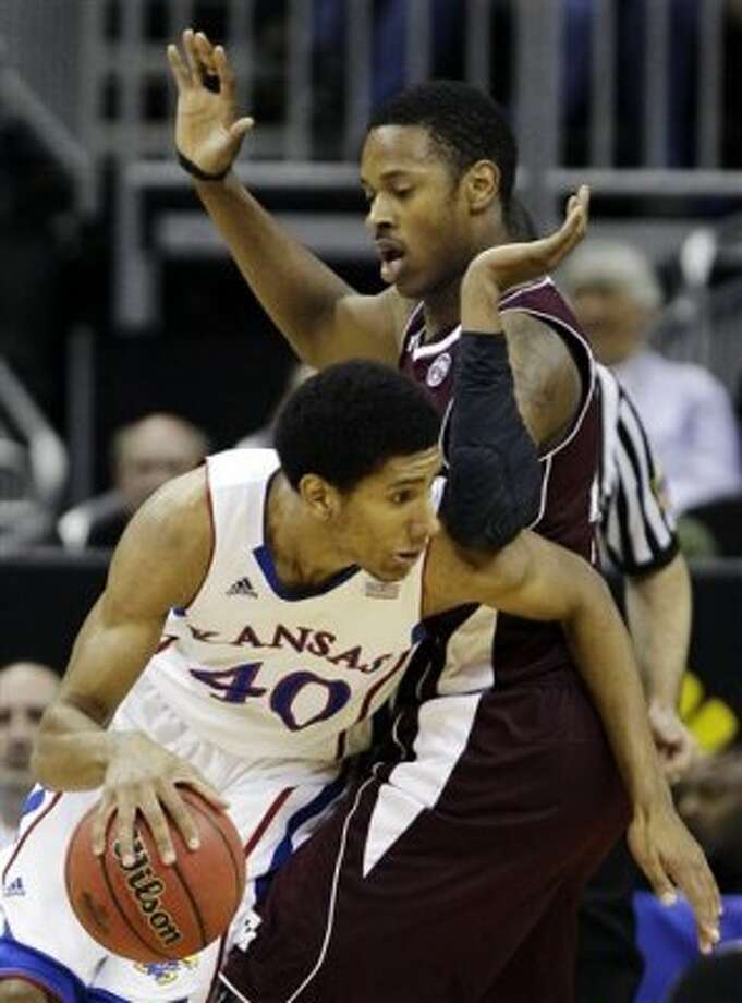 Texas A&M center Keith Davis (4) pressures Kansas forward Kevin Young (40) during the first half of an NCAA college basketball game in the Big 12 Conference tournament, Thursday, March 8, 2012, in Kansas City, Mo. (AP Photo/Charlie Riedel) (AP)