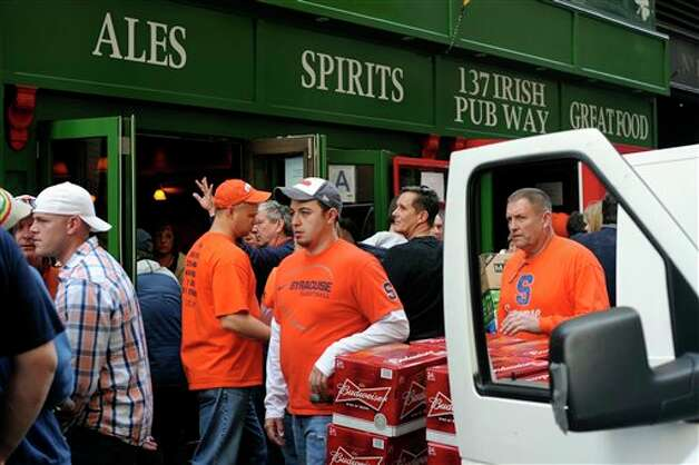 Syracuse  fans walk past a beer delivery van in front of the Blarney Rock Pub in  the Manhattan borough of New York, Thursday, March 8, 2012, following an  NCAA college basketball game in the Big East Conference tournament  between  Syracuse and Connecticut. Syracuse  won 58-55. (AP Photo/Jeffrey Furticella)
