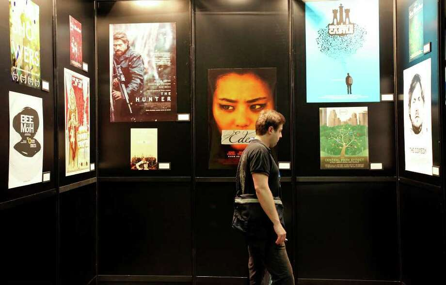 """Andrew Fuller, producer of the film """"Brute Force,"""" looks at film posters at the Austin Convention Center. Photo: EDWARD A. ORNELAS, SAN ANTONIO EXPRESS-NEWS / © SAN ANTONIO EXPRESS-NEWS (NFS)"""