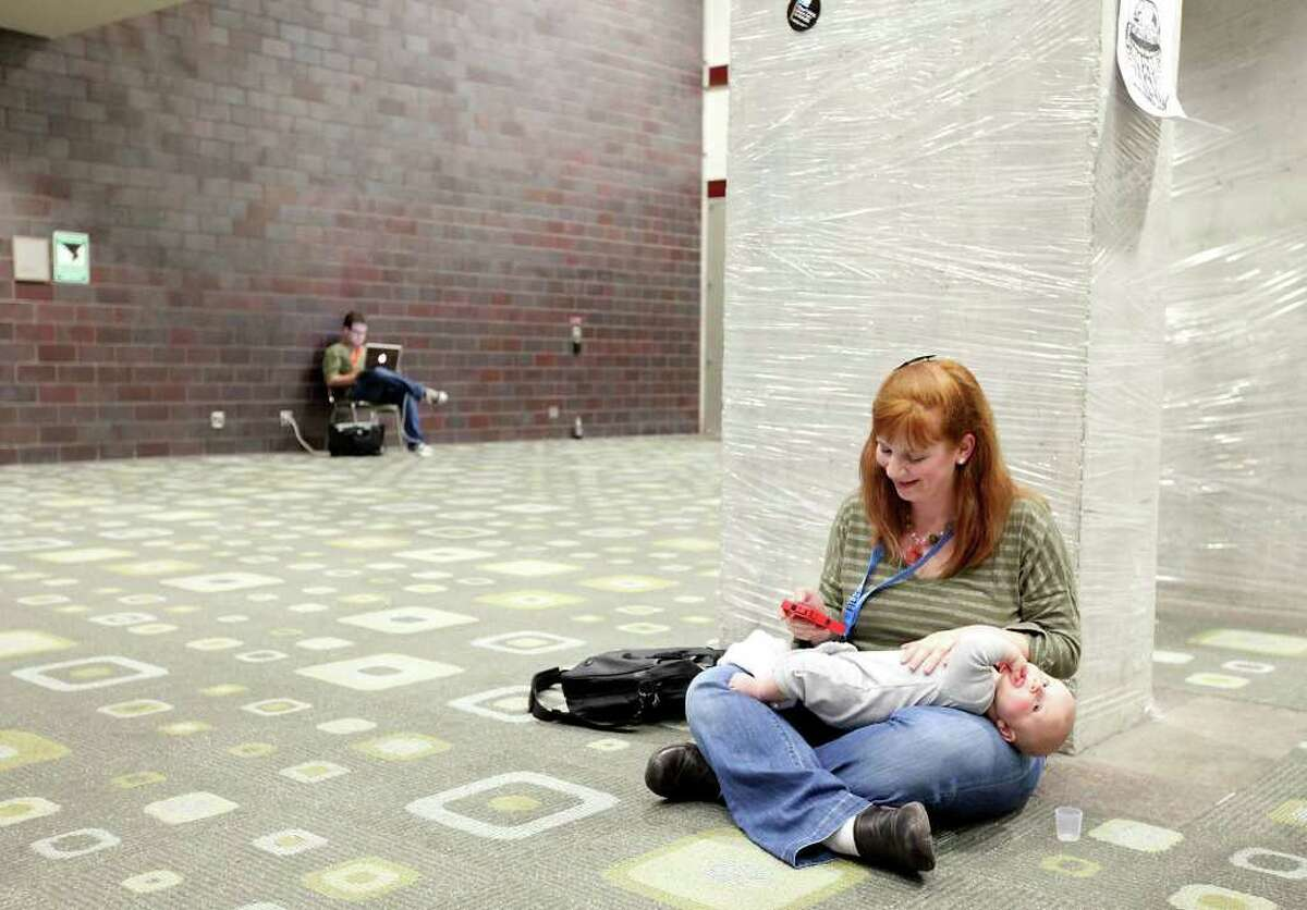Ryan Winkler, who is attending South by Southwest, relaxes with her four-month-old son Auggie Winkler Herr while waiting for her husband Tim Herr (not pictured) to pick up badges for the festival at the Austin Convention Center.