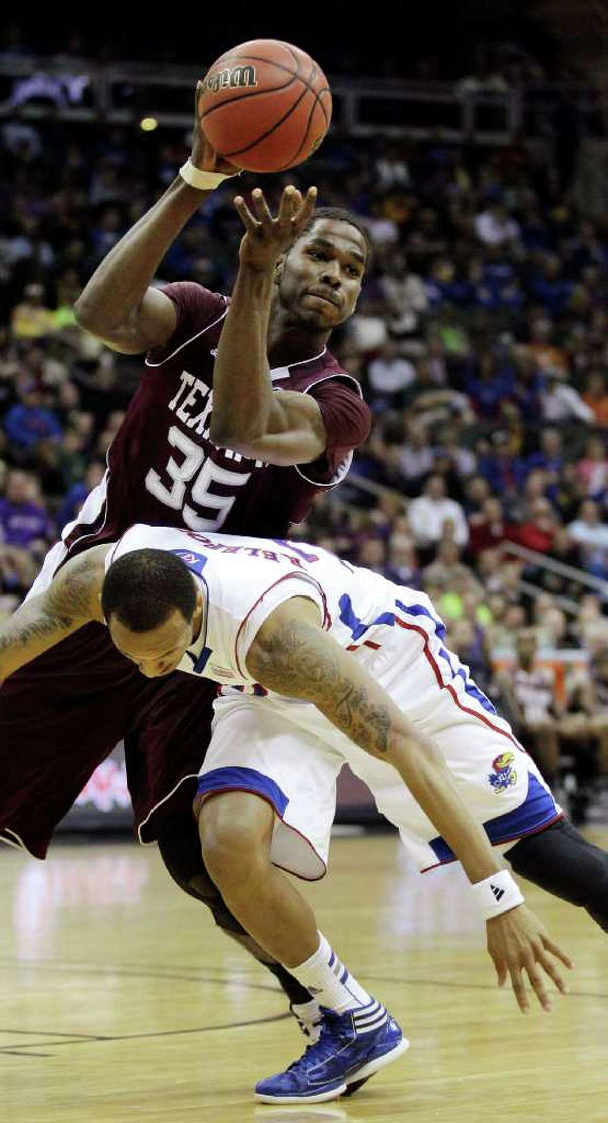 Texas A&M forward Ray Turner (35) passes the ball over Kansas guard Travis Releford (24) during the first half of an NCAA college basketball game in the Big 12 Conference tournament, Thursday, March 8, 2012, in Kansas City, Mo. (AP Photo/Charlie Riedel)