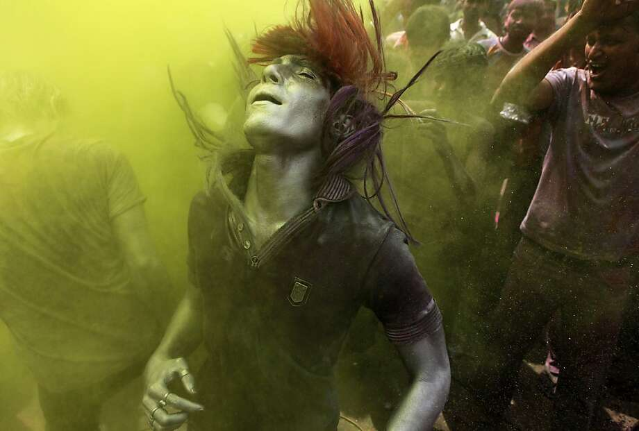 An Indian man dances amid a cloud of colored powder during Holi celebrations in Gauhati, India, Thursday, March 8, 2012. Holi, the Hindu festival of colors, also heralds the coming of spring. (AP Photo/Anupam Nath) Photo: Anupam Nath, Associated Press