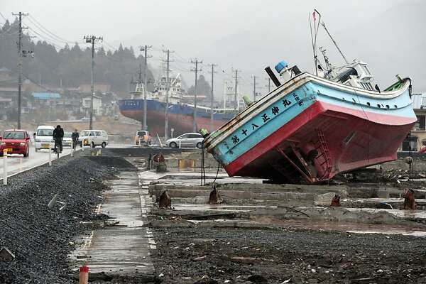 Vehicles move among fishing vessels that were carried from Kesennuma port by the March 11 tsunami, at the Kesennuma city, Miyagi prefecture on March 8, 2012. Japan is readying to mark the first anniversary of the huge earthquake and tsunami that devastated the northeast coast on March 11, sparking a nuclear crisis at Fukushima. More than 19,000 people died in the disaster and hundreds of thousands were made homeless. AFP PHOTO/ TOPSHOTS/ TOSHIFUMI KITAMURA (Photo credit should read TOSHIFUMI KITAMURA/AFP/Getty Images)