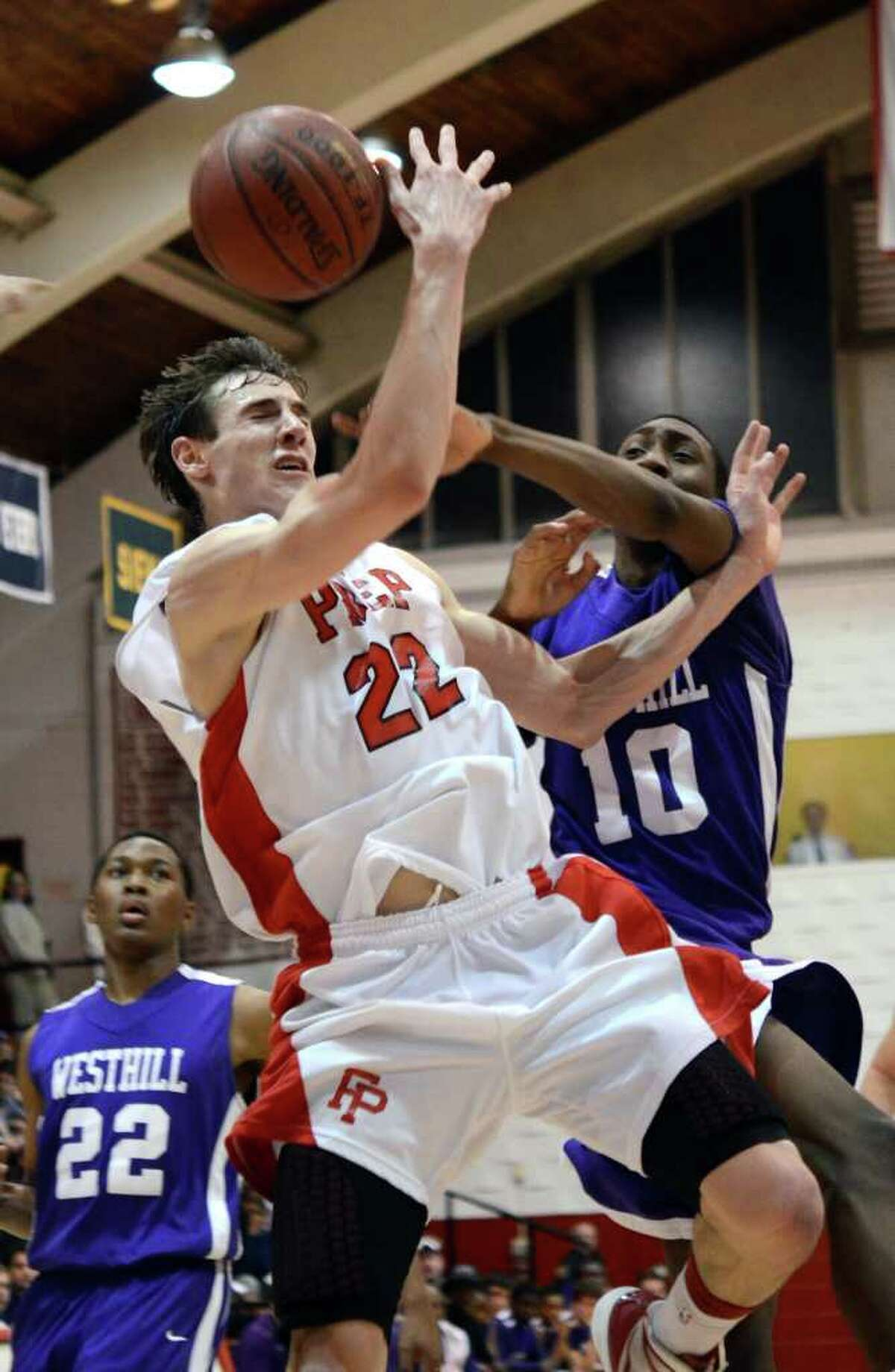 Westhill's Mark Edwin (10) fouls Fairfield Prep's Terry Tarpey (22) during the second round of the Class LL boys basketball state tournament at Fairfield University's Alumni Hall on Thursday, Mar. 8, 2012.