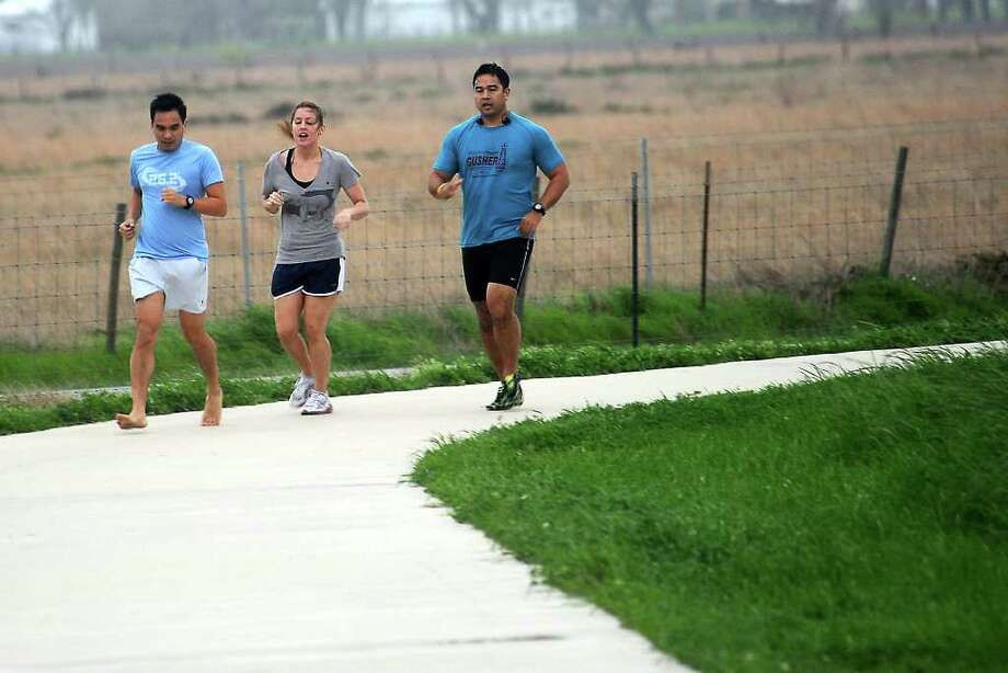 William Fermo, Brittney Sivo, and Jeremy Fermo jog at the Gulf Terrace Hike and Bike Trail in Beaumont, Wednesday, March 7, 2012. The fermo brothers are training to run the Gusher Marathon barefoot or with minimal barefoot sport shoes. Tammy McKinley/The Enterprise Photo: TAMMY MCKINLEY