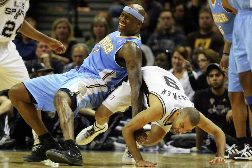 Denver's Al Harrington and Tony Parker take a fall in the second half of the Nuggets's game against the Spurs at the AT&T Center, Sunday, March 4, 2012. The Nuggets beat the Spurs 99-94.