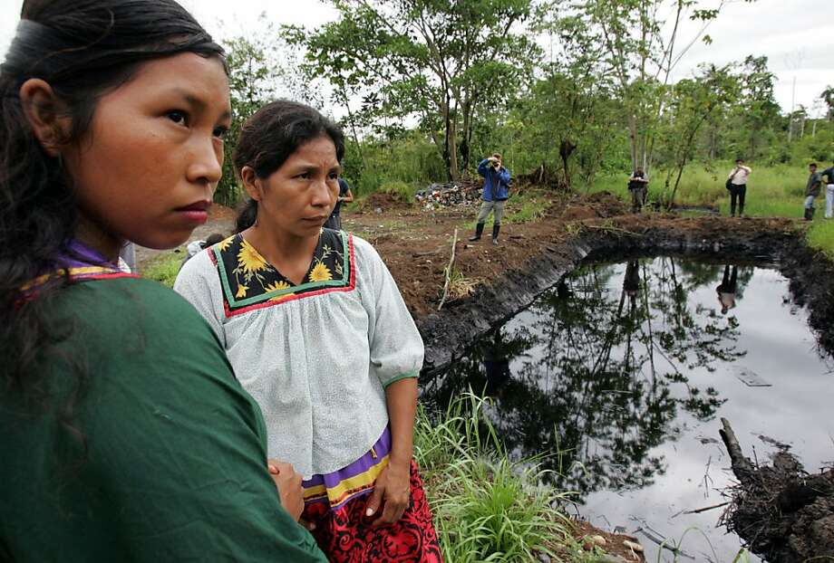 Cofan indigenous women stand near a pool of oil in Ecuador's Amazonian region where Texaco, before being bought by Chevron Corp., was pumping oil and, according to a lawsuit, polluting a Rhode Island-sized expanse of rain forest. Photo: Dolores Ochoa, AP