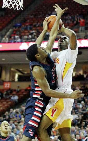 FOR SPORTS - Houston Yates' Clyde Santee drives to the basket against  Denton Ryan's Trey Mohair dur