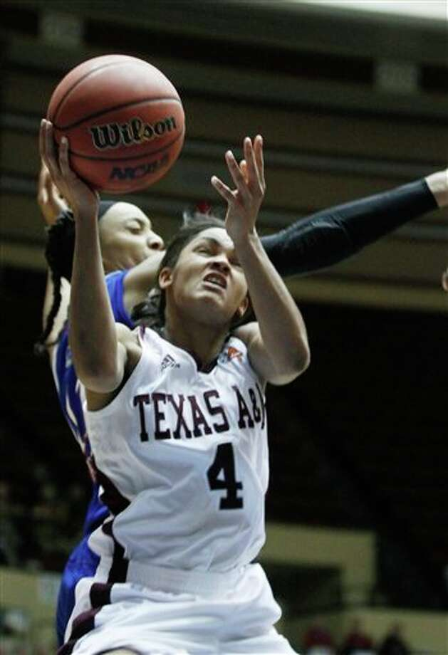 Texas A&M guard Sydney Carter (4) shoots over Kansas forward Chelsea Gardner (15) in the second half of the second round of an NCAA college women's Big 12 conference basketball tournament on Thursday, March 8, 2012 in Kansas City, Mo. (AP Photo/Jeff Tuttle) Photo: Associated Press