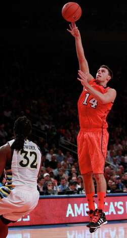 Louisville's Kyle Kuric (14) shoots over Marquette's Jae Crowder (32) during the second half of an NCAA college basketball game in the quarterfinals of the Big East Conference tournament in New York, Thursday, March 8, 2012. Kuric scored 20 points as Louisville won the game 84-71. Photo: Frank Franklin II