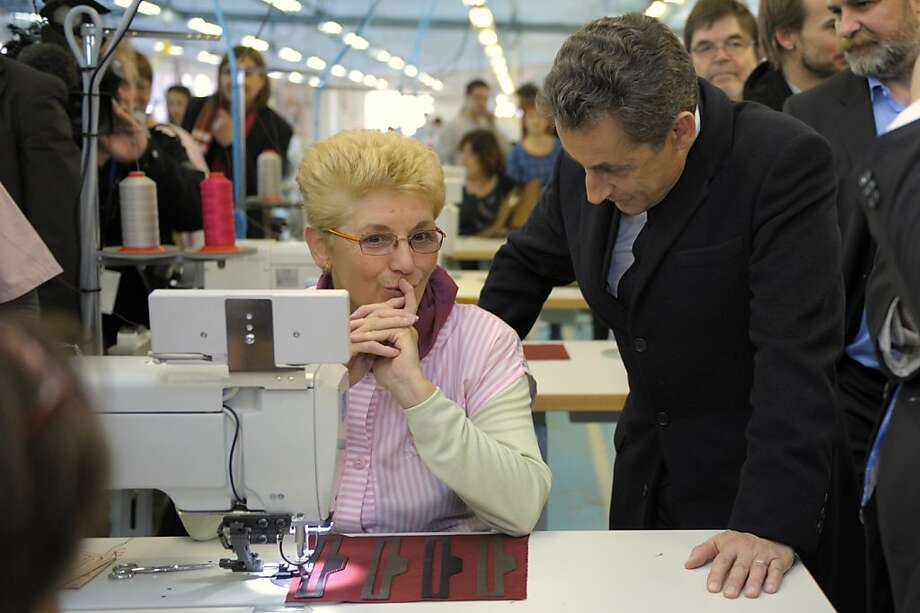 French President and candidate for the 2012 Presidential Elections Nicolas Sarkozy, right, speaks with a Lejaby employee as he visits the Meygal workshop, which replaces the Lejaby factory in Yssingeaux, central France, during a campaign rally focuses on the International Women's Day, Thursday, March 8, 2012. Photo: Philippe Wojazer, Associated Press