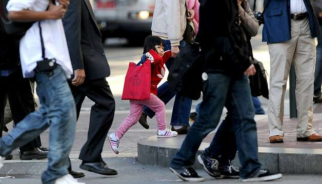 Surrounded by adults, a child crosses a Market St. intersection on Thursday, March 8, 2012, in San Francisco. The Board of Supervisors is holding a special committee hearing on family flight and why so many families with young kids are fleeing the city. Photo: Noah Berger, Special To The Chronicle