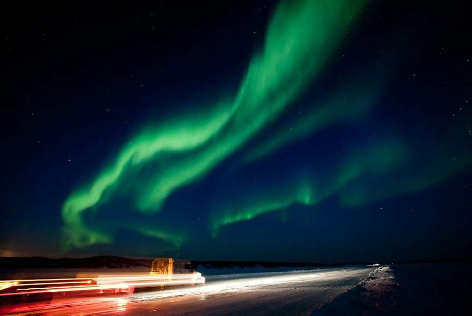 """The largest solar storm in five years sent a huge wave of radiation into earth's atmosphere creating a brilliant show of the aurora borealis near Yellowknife, North West Territories on Thursday March 8, 2012.  Yellowknife, which is situated directly under the auroral """"oval"""", has some of the best northern lights viewing in the world. Truckers returning from the diamond mines 330 kilometers northeast enjoy the nighttime spectacle as they cruised down the ice road on Prosperous Lake. (AP Photo/The Canadian Press, Bill Braden) Photo: Bill Braden, Associated Press"""
