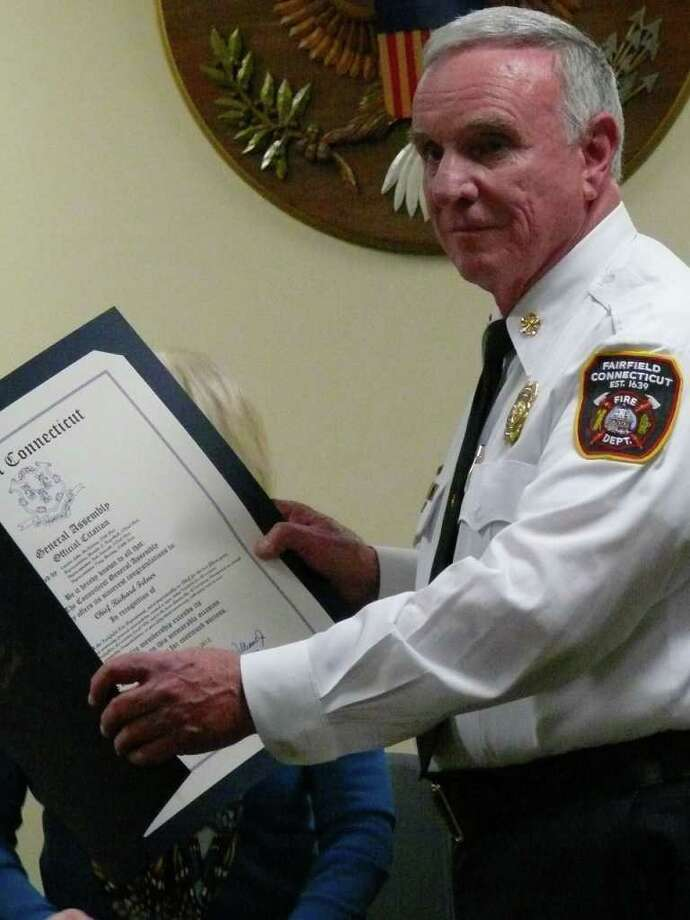 Fairfield Fire Chief Richard Felner with a citation from the state legislature saluting him on 53 years of service with the Fire Department. He was presented the citation at the Fire Commission meeting on Thursday night. Photo: Genevieve Reilly / Fairfield Citizen