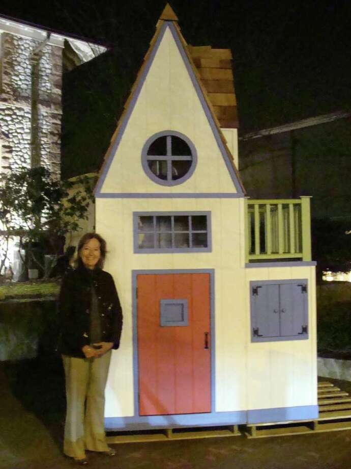 "Theresa Roth, the conceptual artist behind a giant ""birdhouse,"" really a children's playhouse, stands next to the creation Thursday during Project Return's 17th annual Birdhouse Stroll. The birdhouse playhouse is 11 1/2 feet tall and features several doors, a peek hole and an interior ladder to a balcony. Photo: Meg Barone / Westport News freelance"