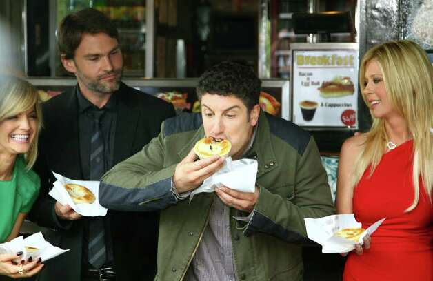 """American Reunion"" cast member Jason Biggs, second from right, bites into a pie as fellow actors Mena Suvari, left, Seann William Scott and Tara Reid, right, watch during a promotional event for the film at the iconic Harry's Cafe de Wheels pie restaurant Tuesday, March 6, 2012, in Sydney.  (AP Photo/Rick Rycroft) Photo: Rick Rycroft, STF"