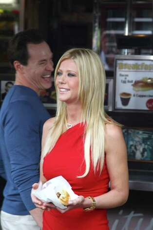 "Actress Tara Reid, right, from the cast of the movie ""American Reunion"" poses for photos at the iconic Harry's Cafe de Wheels pie restaurant as fellow actor Chris Klein walks past, during a promotional event, Tuesday, March 6, 2012, in Sydney. (AP Photo/Rick Rycroft) Photo: Rick Rycroft, STF"