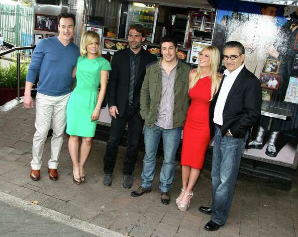 "The cast from the movie ""American Reunion"" from left to right, Chris Klein, Mena Suvari, Seann William Scott, Jason Biggs, Tara Reid and Eugene Levi, pose for photos at the iconic Harry's Cafe de Wheels pie restaurant during a promotional event, Tuesday, March 6, 2012, in Sydney.  (AP Photo/Rick Rycroft) Photo: Rick Rycroft, STF"