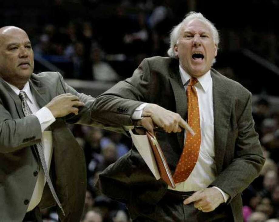 San Antonio Spurs coach Gregg Popovich, right, is held back by assistant coach Don Newman, left, while arguing with officials during the second quarter of their NBA basketball game against the Indiana Pacers in San Antonio, Thursday, March 6, 2008. Popovich was ejected from the game. (AP Photo/Eric Gay) (AP)