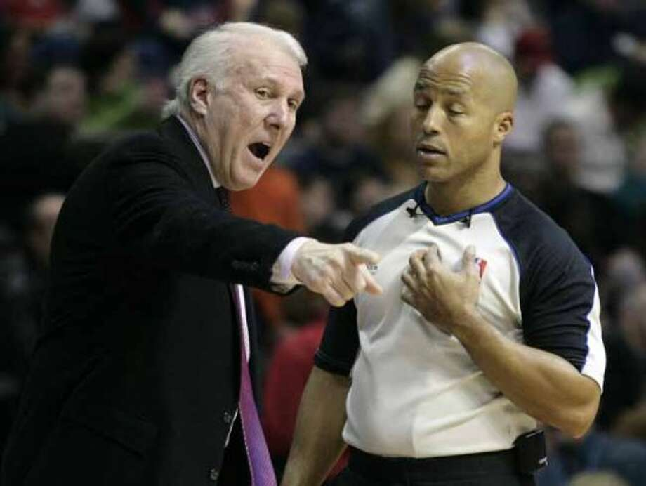 NBA official Marc Davis, right, listens to San Antonio Spurs coach Gregg Popovich make his point in the first half of an NBA basketball game against the Detroit Pistons, Sunday, Feb. 21, 2010, in Auburn Hills, Mich. (AP Photo/Duane Burleson) (AP)