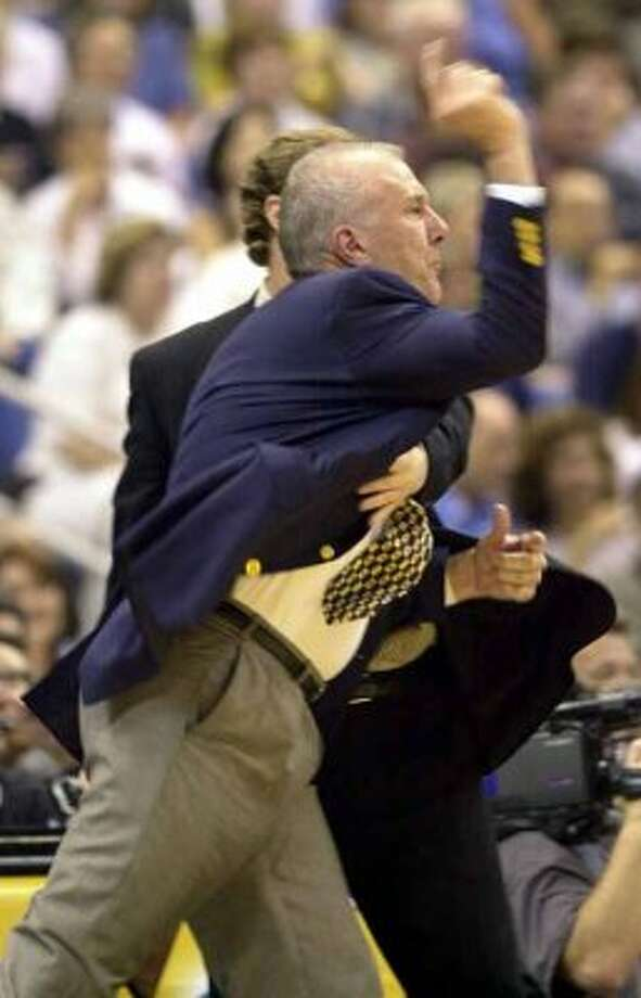 SPORTS/DAILY/STAFF PHOTO BY WILLIAM LUTHER  ---  Spurs head coach Gregg Popovich is restrained by assistant coach Mike Budenholzer after protesting a flagfrant foul call against Danny Ferry. Popovich received a double techincal and was ejected during 2nd period Monday May 7, 2001 at the Alamodome (EN)
