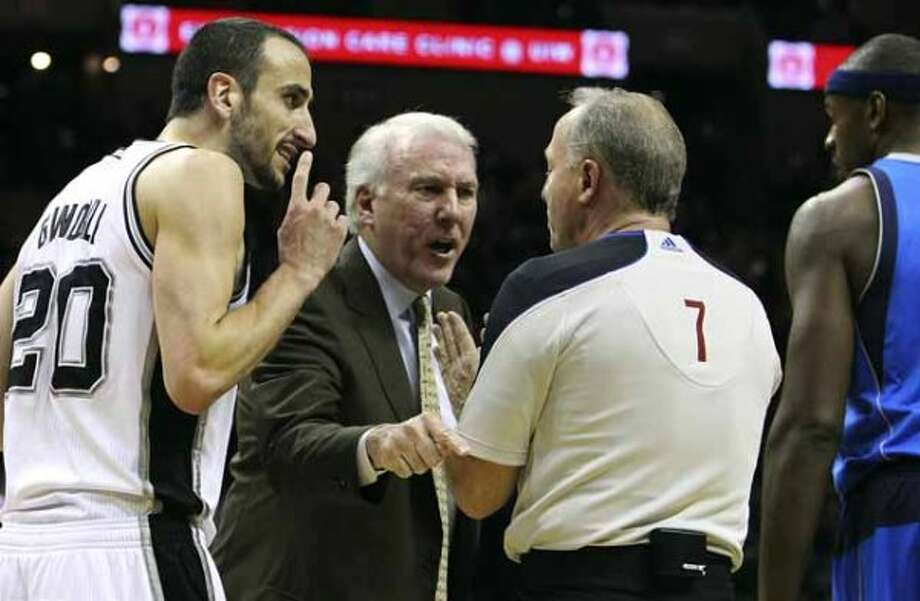 Spurs' coach Gregg Popovich (center) argues with official Kevin Fehr (07) after a questionable play by Dallas Mavericks' Jason Terry on Spurs' Manu Ginobili in the first half at the AT&T Center on Friday, Jan. 14, 2011.  Kin Man Hui/kmhui@express-news.net (SAN ANTONIO EXPRESS-NEWS)