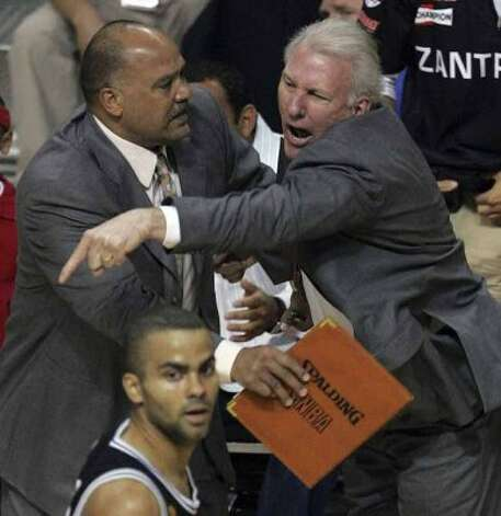 Spurs' coach Gregg Popovich reacts to a technical foul called against him as assistant coach Don Newman holds him back during first  quarter action game four of the NBA Finals at The Palace of Auburn Hills near Detroit, Michigan on Tuesday, June 14, 2005. (Kin Man Hui/staff) (SAN ANTONIO EXPRESS-NEWS)