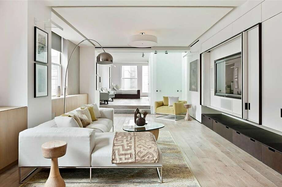 The living/family room features central lighting and a built-in entertainment cabinet to hold and hide a flat-screen television. Photo: Courtesy Of Elliman.com