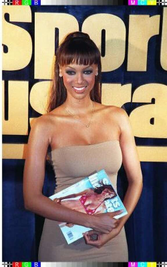 Supermodel Tyra Banks poses with a copy of Sports Illustrated in 1997, age 23. She was the first African American model to appear on the swimsuit issue cover.  (Timothy A. Clary / AFP/Getty Images)