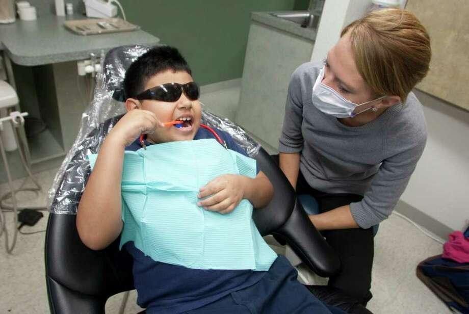Luis Ávalos, de nueve años, recibe instrucciones sobre higiene dental de la estudiante de odontología Bethany Petersen, en la clínica comunitaria Denver Harbor. Photo: Patric Schneider / Houston Chronicle