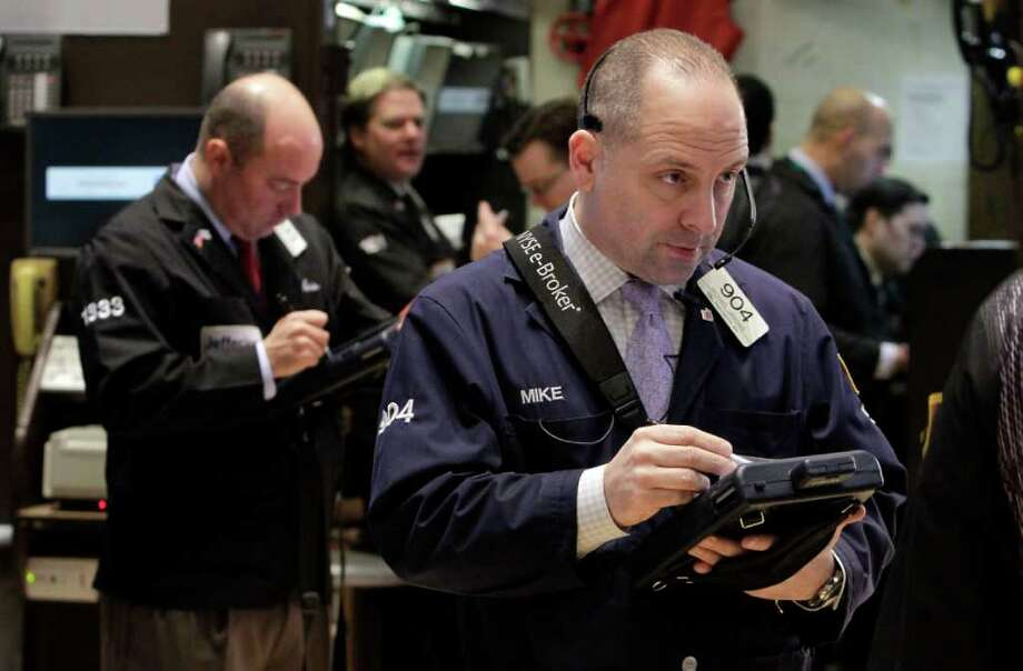 Michael Urkonis, right, works with fellow traders on the floor of the New York Stock Exchange, Friday, March 9, 2012. Stocks rose Friday morning after the February jobs report bolstered hopes that the economic recovery is on track. (AP Photo/Richard Drew) Photo: Richard Drew / AP